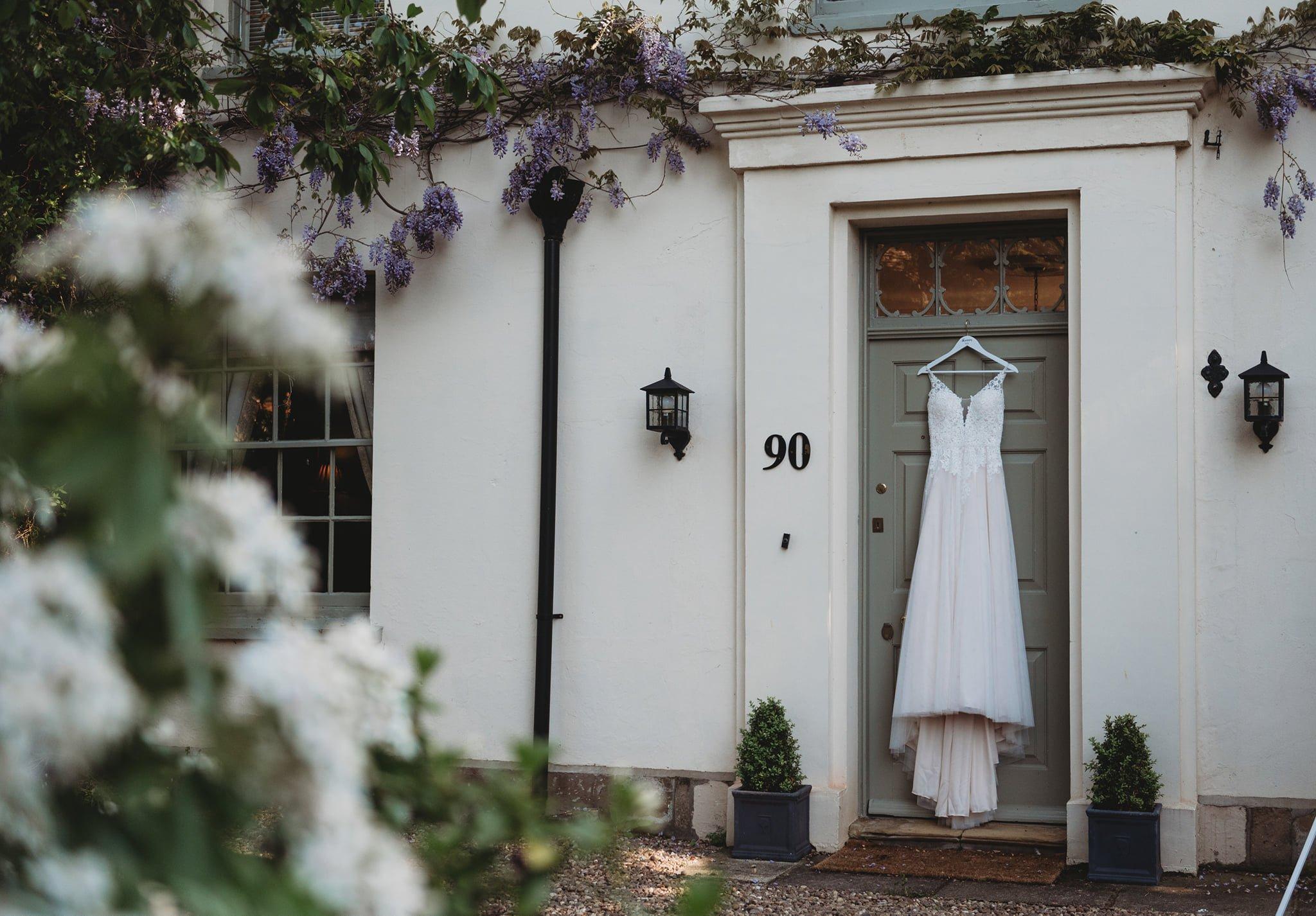 A wedding dress hanging on the door of The Elm Tree Wedding venue